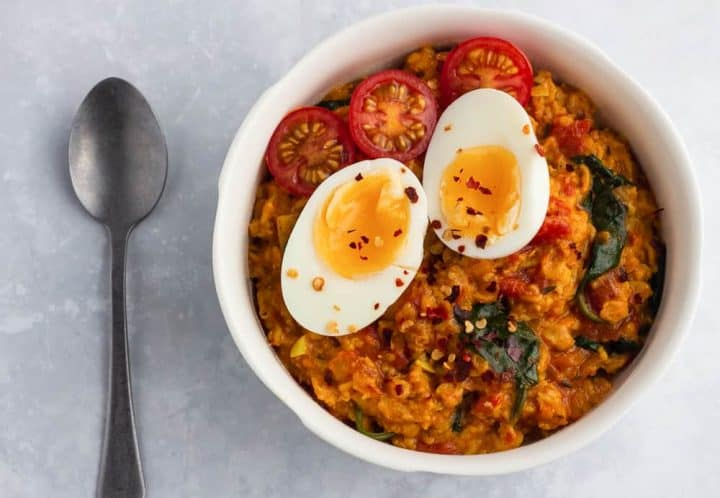 Savoury oats with jollof flavours in a bowl, topped with eggs