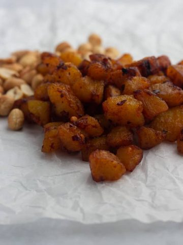 Kelewele | Spicy fried plantain on paper served with peanuts