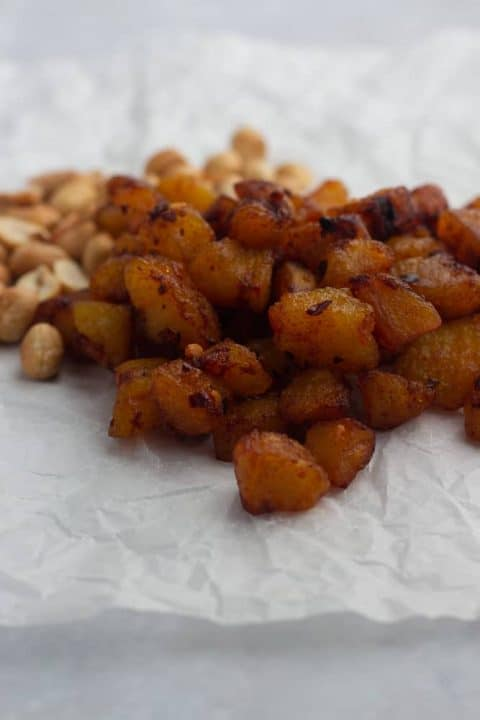 Kelewele   Spicy fried plantain on paper served with peanuts