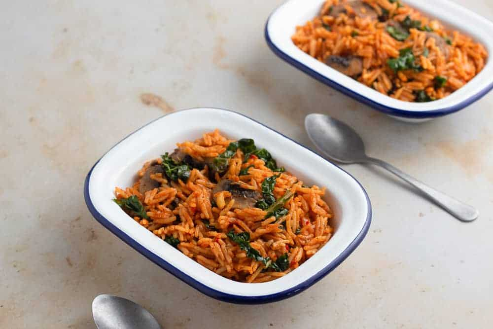 Vegetarian jollof rice with mushroom and kale in a bowl, with spoons on the side.