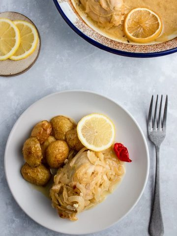 Yassa chicken on a plate with some roast potatoes