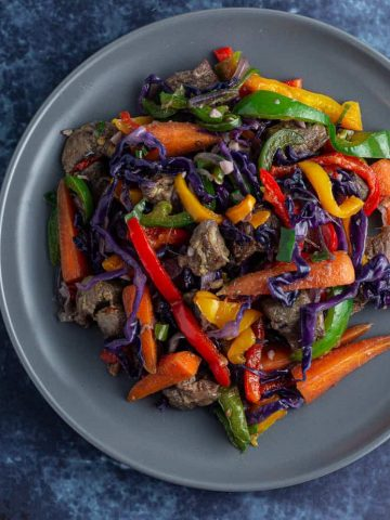 Asun meat with peppers, carrots and purple cabbage warm salad on a flat plate.