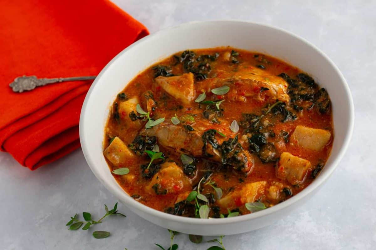 Cocoyam, kale and fish soup in a bowl, with fresh thyme garnish.