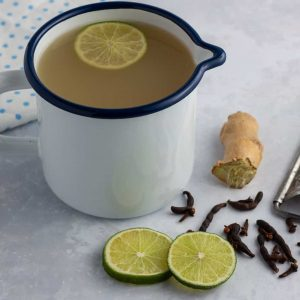 Lamugine   Spicy West African Ginger Drink in a cup with a slice of lime