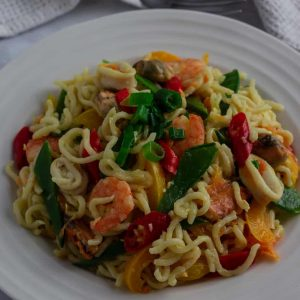 Nigerian Indomie noodles with vegetables and seafood in a bowl