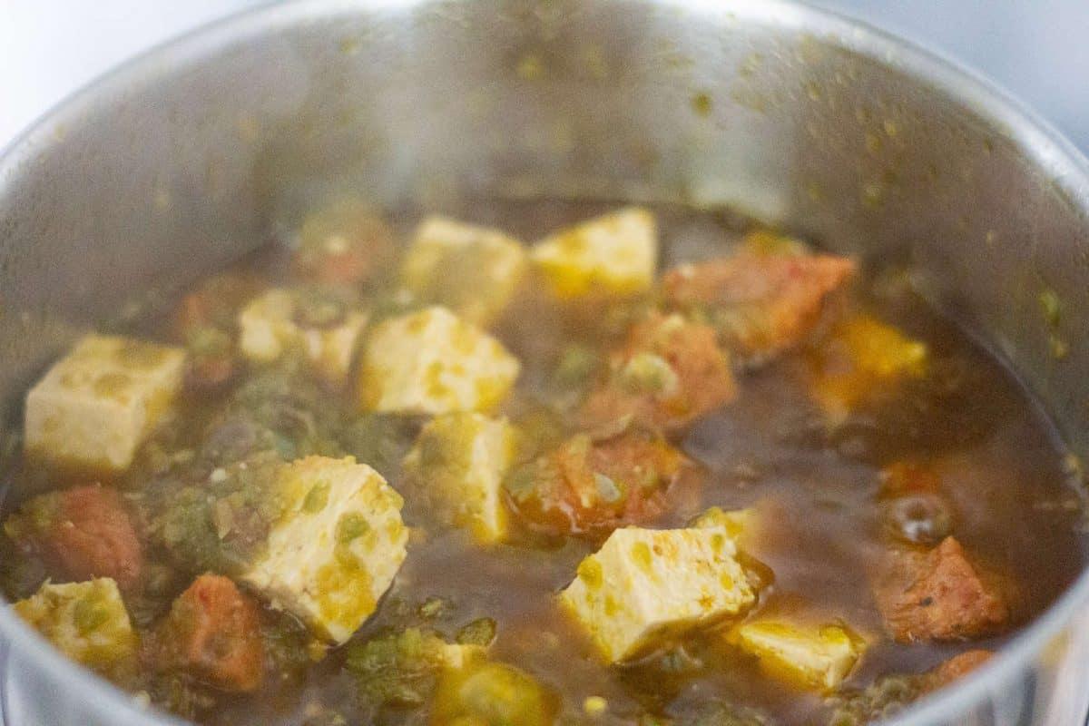 Vegetarian Ayamase with tofu and vegan sausages in a pot