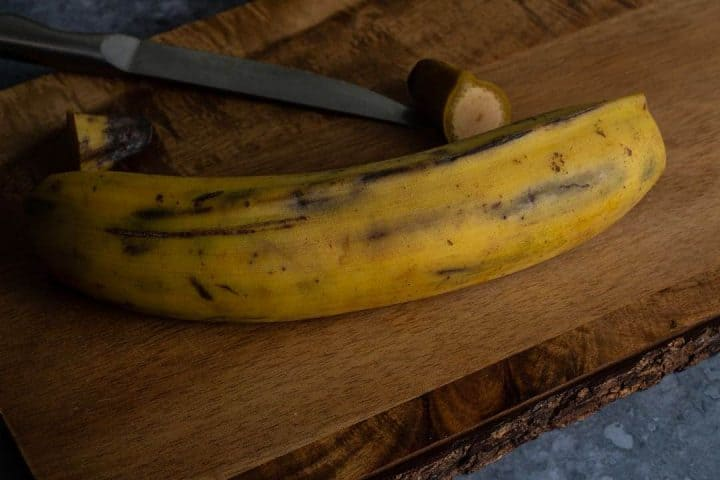 Plantain with both ends cut off ready for peeling