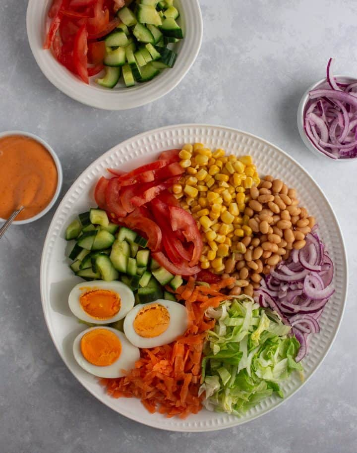 Nigerian salad ingredients laid out on a white plate