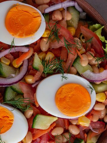Nigerian salad with dill topping in a wooden bowl
