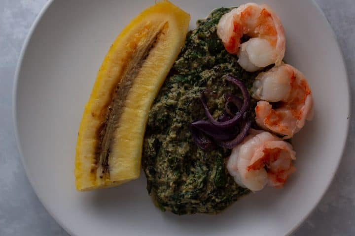 Ndole (Cameroonian bitter leaf stew) with prawn and onion toppings; served with boiled plantain