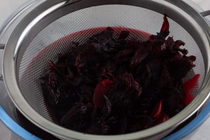 Cooked hibiscus calyces draining in a sieve